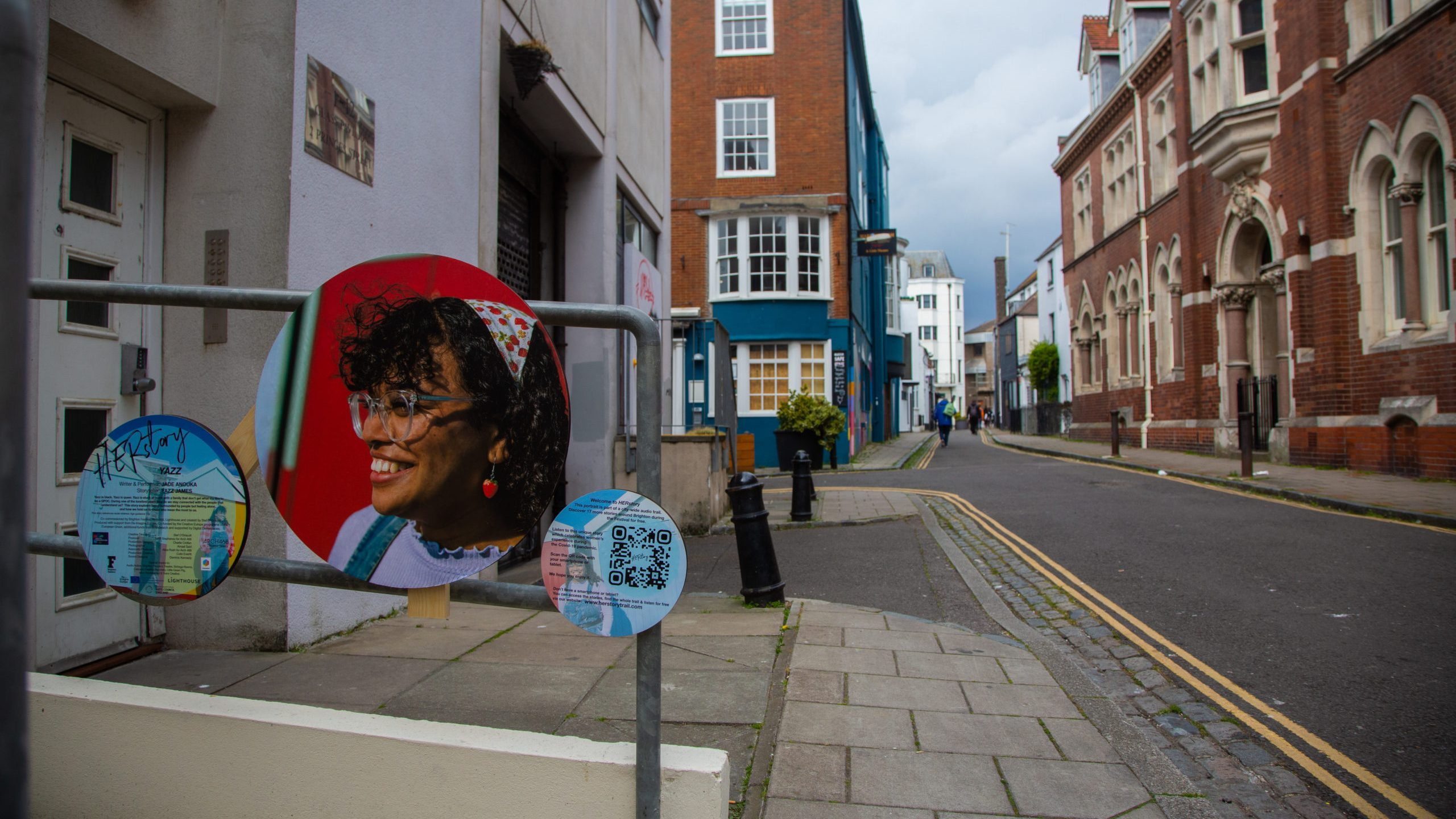 Image shows a circular public artwork in a street. It features a smiling woman on a red background