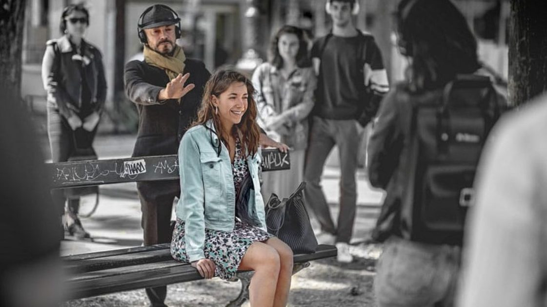A woman sits on a bench smiling while a bearded man stands behind her with his hand pointing towards her